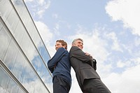 Germany, Hamburg, Two businessmen standing back to back, low angle view