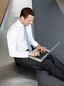 Germany, Cologne, Businessman sitting on bench in corridor using laptop, portrait