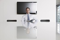 Germany, Cologne, Businessman sitting in conference room (thumbnail)