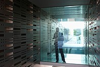Germany, Cologne, Businessman standing behind glass door, using mobile phone