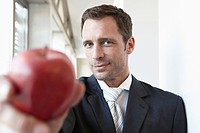 Germany, Cologne, Businessman holding apple, portrait, close_up