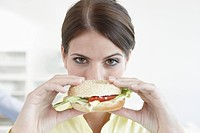 Germany, Cologne, Businesswoman holding sandwich, portrait, close_up