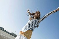 Germany, Berlin, Young woman raising her arms in empty parking lot, smiling