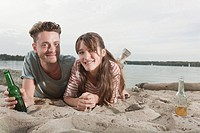 Germany, Berlin, Lake Wannsee, Young couple lying on beach, smiling, portrait