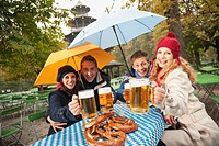 Germany, Bavaria, English Garden, Four persons sitting in rainy beer garden