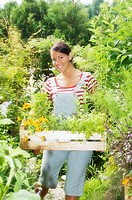 Austria, Salzburger Land, Woman carrying wooden box with plants
