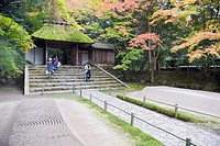 Sand garden, autumn colours and moss covered entrance with visiting tourists, Honen in temple dating from 1680, Kyoto, Japan