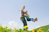 Germany, Bavaria, Munich, Mother swinging daughter 6_7 on meadow, fooling about