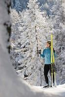 Austria,Tyrol, Seefeld, Wildmoosalm, Woman holding cross_country skis