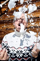 Italy, South Tyrol, Seiseralm, Senior woman throwing snow into the air, eyes closed, portrait