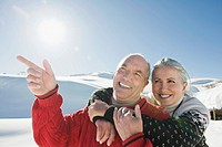 Italy, South Tyrol, Seiseralm, Senior couple in winter scenery, man pointing, portrait, close_up