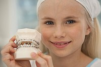 Germany, Bavaria, Landsberg, Girl 8_9 holding model of braces, portrait, close_up