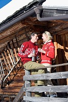 Italy, South Tyrol, Seiseralm, Couple standing on deck of log cabin, holding thermos flask (thumbnail)
