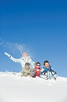 Italy, South Tyrol, Seiseralm, Family sitting in snow, laughing