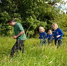 An education officer with the Forestry Commission in wales leading a group of primary school children on a bug hunting nature trail, UK