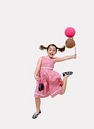 Girl jumping up in the air with purse and balloons - about to go to party