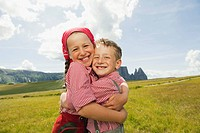 Italy, Seiseralm, Boy 6_7 and girl 8_9 in field, embracing, smiling, portrait