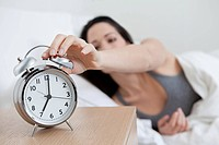 Young woman reaching for alarm clock (thumbnail)