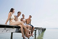 Germany, Bavaria, Ammersee, Young people sitting on jetty, smiling, portrait