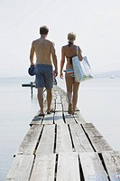 Germany, Bavaria, Young couple wearing swimwear walking on jetty, rear view