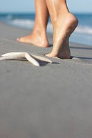 Italy, Sardinia, Woman´s feet walking on sandy beach