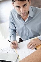 Businessman sitting at desk holding ballpen, portrait, elevated view