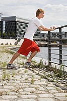 Germany, Berlin, Young man stretching on railing