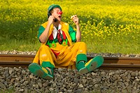 Clown Sitting On Railroad Tracks And Talking On The Phone