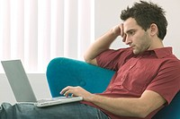 Twenty Something Caucasian Male Sitting On A Sofa And Using A Laptop