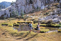 Hikers Walking Through A Wet Meadow Between Rocky Cliffs