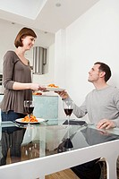 Woman passing plate to husband