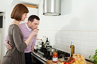 Man tasting pasta sauce that wife is making