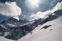 A strong sun shines upon the snowy mountains, Picos de Europa, Asturias, Spain
