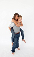 Young boy giving his girlfriend piggyback ride against white background