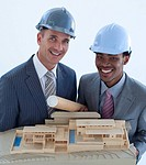 Smilingengineers with hard hats holding a model house and blueprints