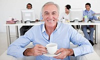 Senior businessman drinking a coffee with his team in the background