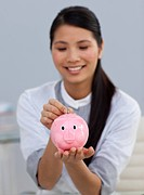 Smiling businesswoman saving money in a piggybank in the office