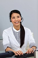 Ethnic businesswoman with headset on at her desk