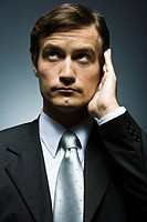 Businessman with hand cupped around ear listening attentively