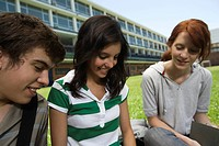 Teenage friends hanging out, sitting together outdoors on school lawn