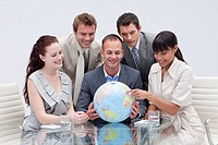 Business team holding a terrestrial globe in the office