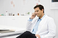 Doctor taking phone call in office