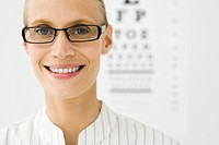 Young woman wearing glasses, eye chart in background, portrait