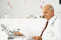 Doctor at desk busy with paperwork
