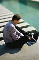 Businessman sitting on ground beside pool, using laptop computer