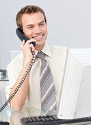Smiling businessman talking on phone and working with a computer in the office