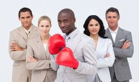 Smiling Afro_American businessman with boxing gloves leading his confident team