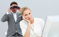 Charismatic manager holding binoculars looking at his colleague´s computer in the office