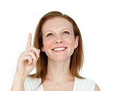 Enthusiastic businesswoman pointing at a copyspace isolated on a white background