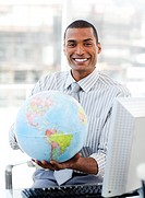 Ethnic businessman holding a terrestrial globe in his office